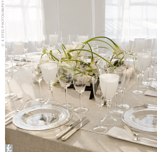 The square tables at Shari and Evan's reception were topped with a menagerie of low, rectangular vases filled with black river rocks and hand-sculpted white calla lilies. Each arrangement connected to the next with textural grass pieces.