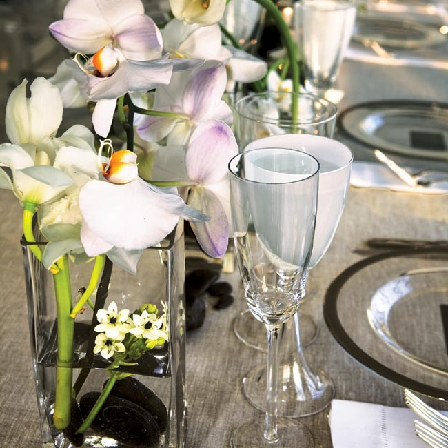 "The long banquet tables at Shari and Evan's reception were topped with a series of low, rectangular, clear glass vases filled with orchids and calla lilies, each connected to the next to create a ""hop"" affect from vase to vase."