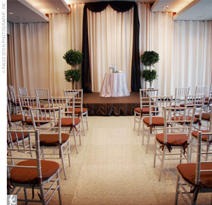 Two topiary trees flanked the altar, and chairs were set up to form one center aisle.