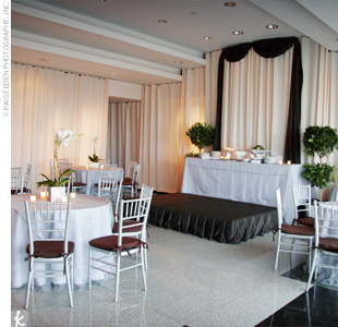 Following the ceremony, the room was transformed for the reception. Tables were draped with white cloths and silver shimmer overlays, and white frosted votives glowed all around for a romantic feel.