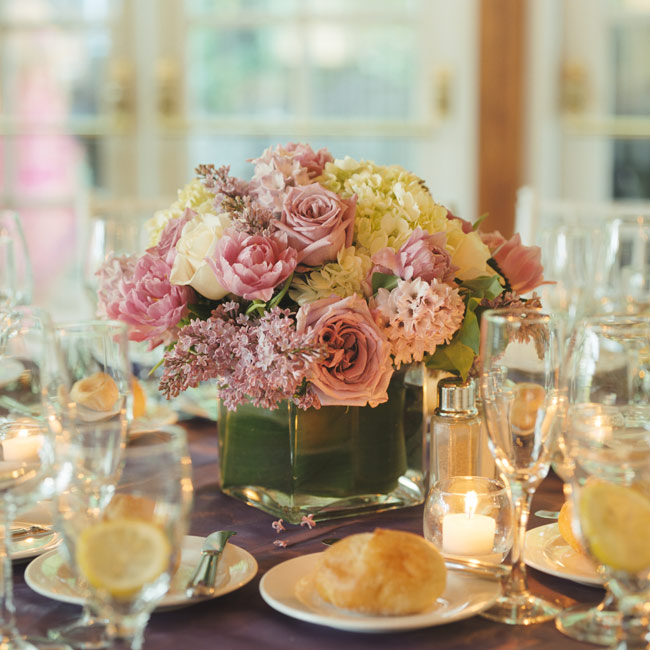 Kimberly wanted to make sure everyone could chat easily over the reception tables, so she chose low floral centerpieces filled with purple, cream, and green flowers and set into square glass vases.