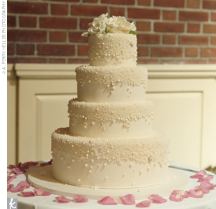 The four-tiered ivory cake was covered with fondant and decorated with different-sized, white and ivory, sugar pearls. To top it off, white peonies and roses were placed on the top tier.