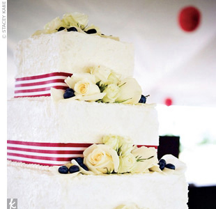 The three-tiered square cake was decorated with red-and-white-striped ribbon, white roses, and blueberries on each tier.