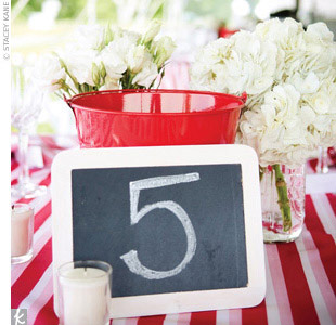 The bride drew table numbers on white-framed chalkboards that were propped up against the mason jars. Red pails were also on hand to collect the shells from lobsters (the main course!).