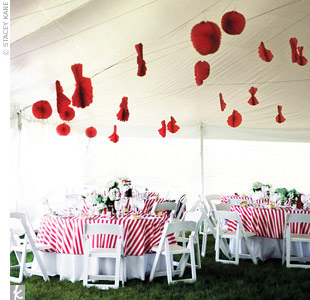 A big white tent was strung with red paper lanterns and filled with round tables for the couple's 78 guests. Each table was draped with a red-and-white-striped overlay and topped with three mason jars filled with white roses, white lisianthuses, and white hydrangeas.