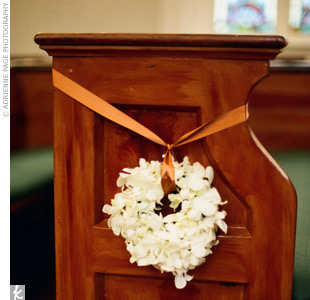 For Christine and Erics Jewish wedding in Charleston, wreaths of white dendrobium orchids tied with copper ribbon hung from the synagogues pews.