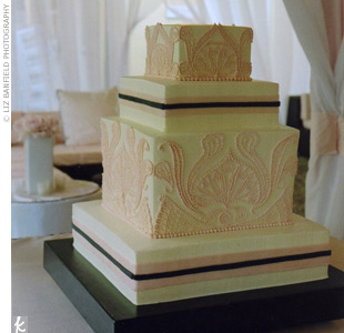 Inspired by the invitations, the four-tiered, white buttercream cake had alternating layers decorated with pink paisley and pink and white ribbons. The cake was displayed on a black lacquered cake stand.