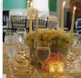 To create a clean, romantic setting, the tables had square centerpieces filled with peonies, lisianthus, and fragrant gardenias surrounded by four tall candles. Custom hemstitched linen napkins printed with the couples monogram added a personal touch to each place setting.