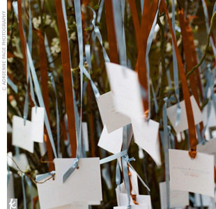 A large, blooming cherry tree served as the perfect display for white escort cards hung with copper and blue satin ribbon. Each card had the guest's name printed in matching ink. 