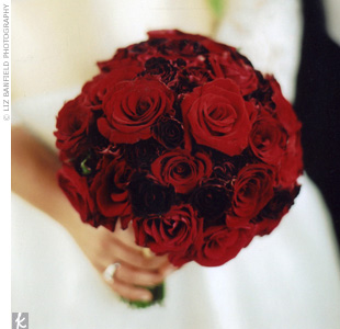 The bride carried an overflowing bouquet of fully opened red roses.