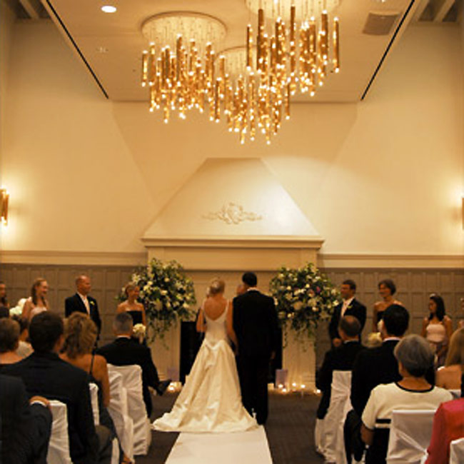 Jenni and Jon stood in front of a large white fireplace illuminated with candles and two large sprays of flowers on five-foot stands.