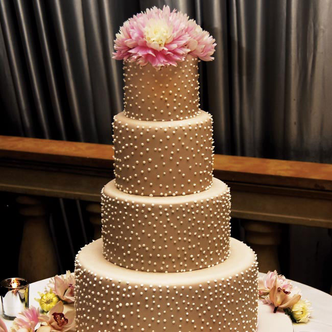 Jenni and Jon's four-tiered round cake was hazelnut-flavored with apricot filling.  Taupe-colored fondant and white pearl dots covered the layers, while the top tier featured smaller pink and rose-colored dinner plate dahlias.
