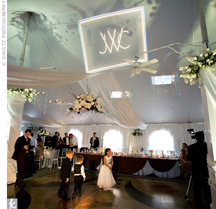 For dramatic effect, white spotlights were placed on the floor at the base of each tent pole and along the walls of the tent. A spotlight of Cara and Jason's monogram shone on the ceiling above the dance floor.