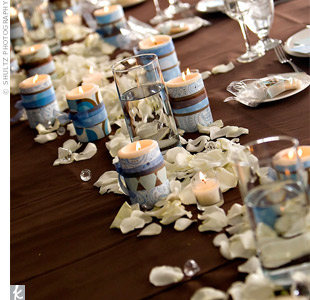 Cara and Jason, along with their bridal party, sat at a long table topped with a chocolate-brown tablecloth, white rose petals, and candles wrapped in patterned paper.