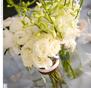 Reception tables were adorned with glass vases filled with peonies, calla lilies, fern fronds, tulips, roses, and hydrangeas. Votives added a soft glow to the tables.