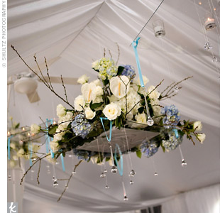 As the crowning glory over the dance floor, Cara and Jason had a large floral arrangement of roses and hydrangeas suspended on a square piece of Plexiglas. Additional pieces of Plexiglas held candles and crystals, which glittered overhead.