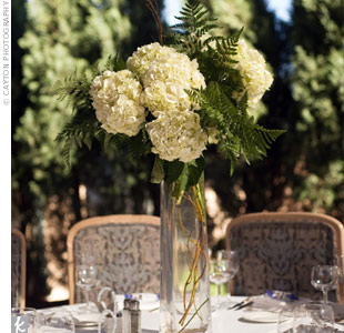 The couple chose a mix of centerpieces in various heights to add a little drama to the tables. For the tall arrangements, they used cream hydrangeas with lemon leaf and willow branches.