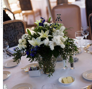 The shorter arrangements were a mix of white lilies, hydrangeas, stock, and lisianthus with blue delphinium accents.