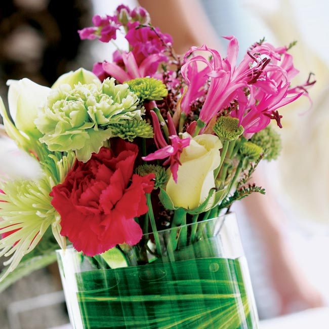 The tabletop decorations consisted of two different arrangements. One was a partially submerged orchid in a tall vase topped with a carnation ball; the other was a small, modern floral arrangement that incorporated the pink and green color scheme.