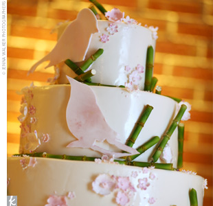 The couple cut into a three-tiered chocolate cake with Baileys Irish cream and lemon-raspberry fillings, adorned with pink flowers, pink birds, and green bamboo stalks.