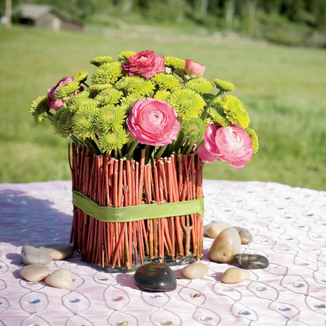 Five different types of centerpieces topped tables, including bright green button mums and raspberry-colored ranunculuses surrounded by river rocks.