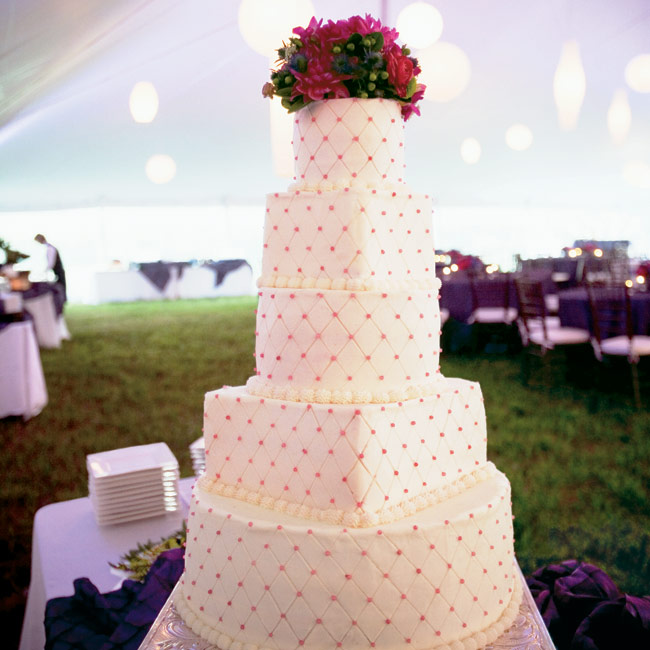 The tall, five-tiered cake was covered in a pin-tuck pattern and accented with edible raspberry-colored pearls.