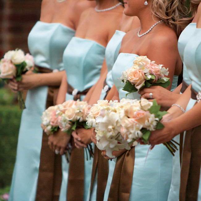 Kasey's bridesmaids carried bouquets filled with white dendrobium orchids and blush pink and cream Anna and Vendela roses tied with brown satin and decorated with studded pearls.