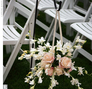 Black shepherd&#39;s hooks with hanging pomanders of white orchids, blush roses, and amaranthus lined the aisle.