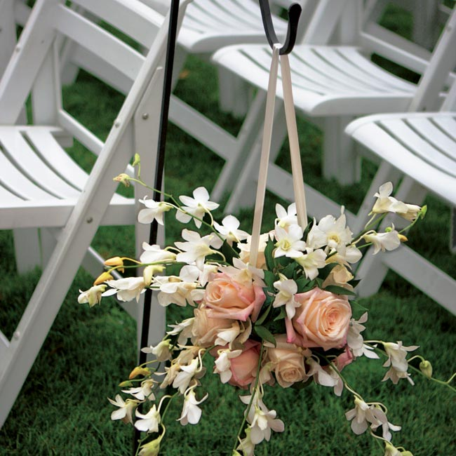 Black shepherd's hooks with hanging pomanders of white orchids, blush roses, and amaranthus lined the aisle.