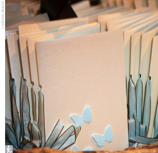 Designed by the bride, the programs were clean and modern with tiny ocean blue-colored butterflies affixed to the covers.