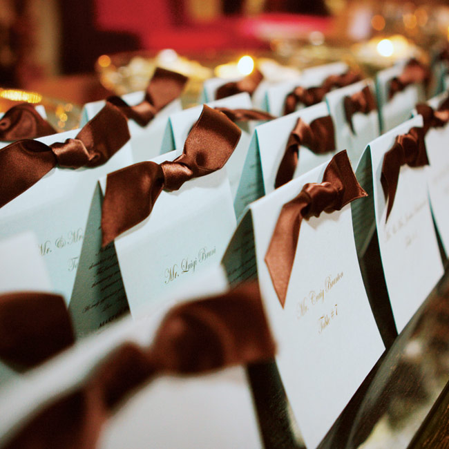 Guests were escorted to their seats by tented blue cards printed with their names and table numbers in brown and accented with a brown ribbon.