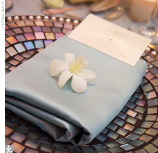 Ocean blue tablecloths with white overlays covered the tables, and silver chiavari chairs added a touch of elegance. Mosaic chargers with a petal edge were topped with ocean blue napkins, menus, and a white cymbidium orchid.