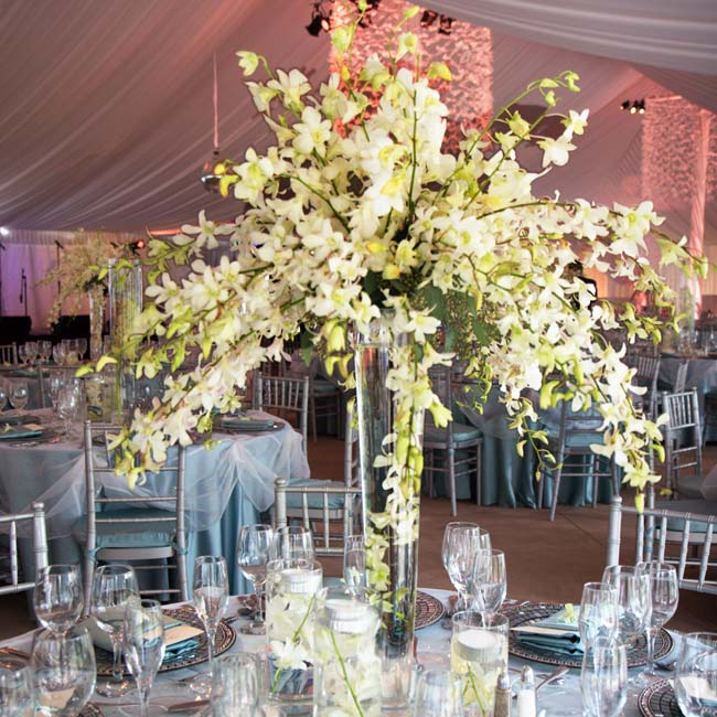 Large, glass, cylinder vases filled with white cymbidium orchid stems sat at the center of each table. Small votive candles lit the arrangements from below.