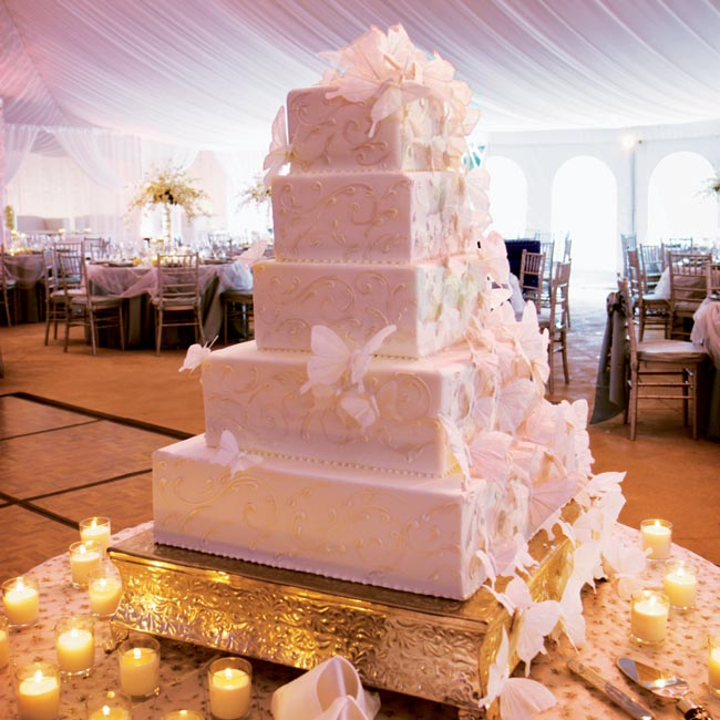 The five-tiered, white fondant–covered, chocolate cake was decorated with a shimmer dusting and over 75 silk butterflies.