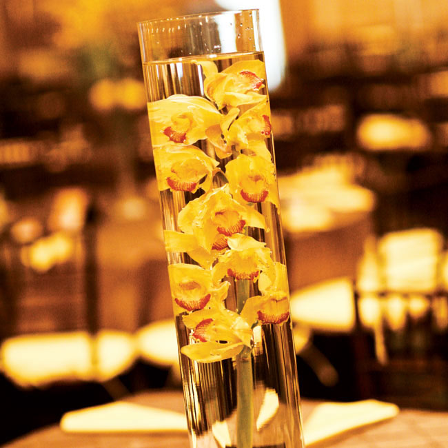 The tables featured glass cylinder vases with stems of full-sized orchids submerged in water.