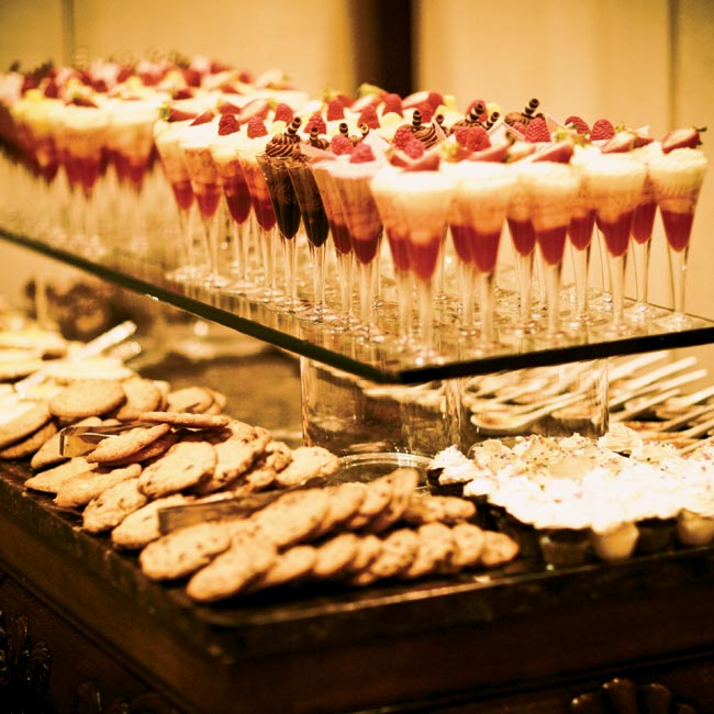 Guests indulged in a variety of tasty treats including croquembouche, chocolate-dipped strawberries, creme brulee spoons, and fresh fruit and berries in martini glasses. Mini ice cream cones filled with banana, coffee, and vanilla ice cream were passed by waiters.