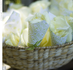 Green, patterned paper cones tied with green ribbons held white flower petals that guests used to shower the couple following the nuptials.