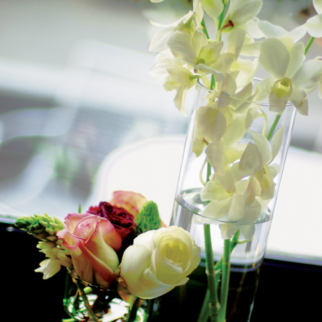 Tall vases filled with white orchids and green hanging amaranthus complemented shorter vases packed with spider chrysanthemums, roses, white stars of Bethlehem, and ranunculuses.