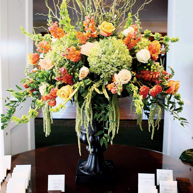 White cards with chocolate brown script directed guests to their seats. A vibrant bouquet of white, orange, yellow, and pink flowers sat on the display table.