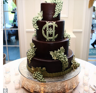 Guests enjoyed a four-tiered chocolate-iced cake filled with layers of chocolate cake and sweet vanilla buttercream icing. Bunches of green, sugar grape clusters highlighted the couple's monogram, while gold and green pleats matching Haley's dress accented the bottom layer.