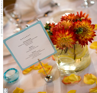 Yellow spider mums and orange dahlias overflowed in vases filled with blue marbles and lemons.