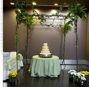 One of the cakes sat beneath a wrought-iron pergola decorated with greenery. Potted mums placed at the base of the structure added a bright pop of color.