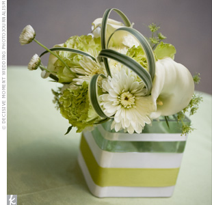 Small arrangements containing blooms like calla lilies and mums were placed in simple, ribbon-wrapped square vases.