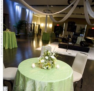 Tables topped with green linens, votive candles, and green and white centerpieces surrounded the dance floor.