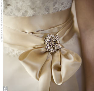 Andrea's ivory, silk organza dress with a pick-up skirt and Alencon lace bolero fit in perfectly with the wedding's Victorian theme. She secured her champagne satin sash at the waist with an elaborate brooch.