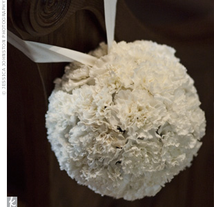 White carnation pomanders hung from the edge of alternating pews.