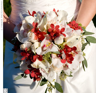 The hand-tied bouquet overflowed with ivory vendela roses, cymbidium orchids and calla lilies. Red mokara orchids and seeded eucalyptus added a touch of color.