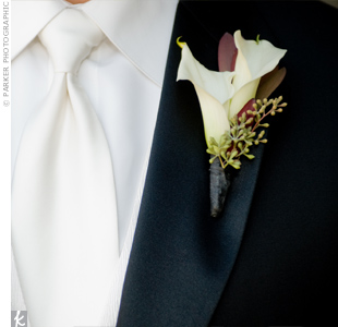 Two mini cream calla lilies with seeded eucalyptus decorated the groom&#39;s lapel.