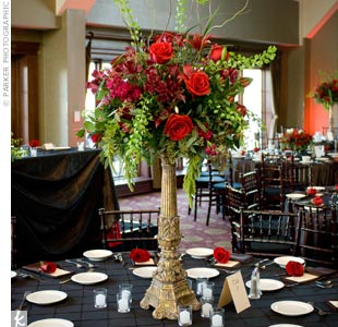 Red roses and orchids, apple-green amaranthus and brown curly willow filled ornate gold-gilded stands.