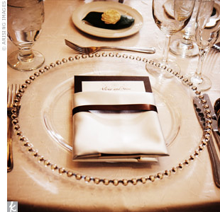 Menus tied with chocolate brown ribbon tucked into white napkins complemented the gold-beaded chargers.